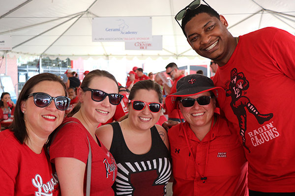 UL Lafayette alumni stop for a photo during tailgating with the Alumni Association